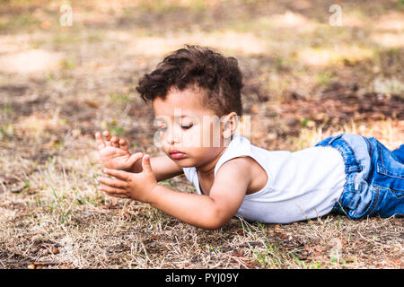 Little boy laying on ground in park outdoor and playing with hands - Stock Photo
