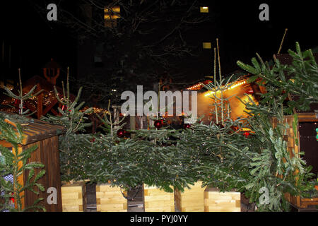 Christmas market in Germany. Sale of christmas tree on evening street - Stock Photo