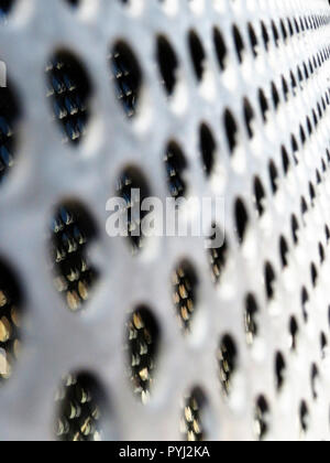 galvanized metal security grill mesh sheet with holes making graphic shapes - Stock Photo