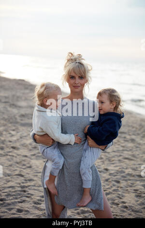 Charming mother carrying her beloved twin sons - summer shot - Stock Photo