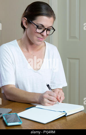 Young woman writing intently in journal with cell phone and laptop at her side. - Stock Photo