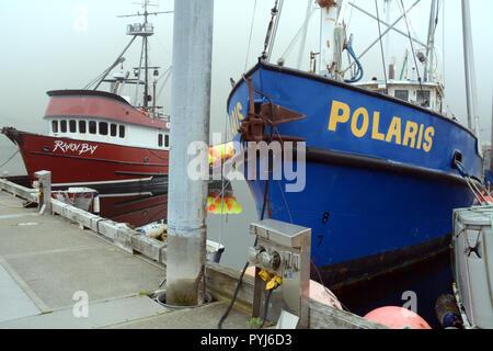 Commercial fishing boats docked at a marina in Dutch Harbor, on Amaknak Island (Unalaska), in the Aleutian Islands chain, Alaska, United States. - Stock Photo