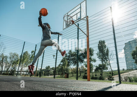 Nice strong man jumping while throwing a ball
