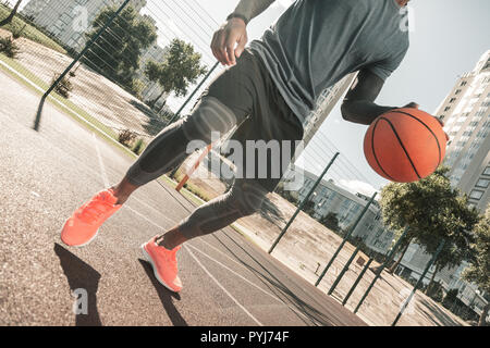 Well built nice man playing basketball alone