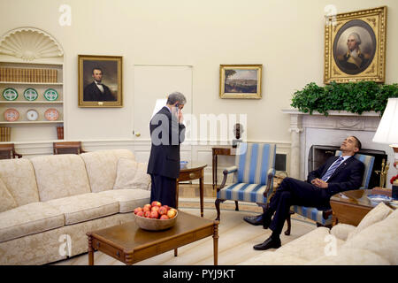 President Barack Obama rests his head on his chair while Chief of Staff Rahm Emanuel talks on cell phone in the Oval Office 2/11/09. - Stock Photo