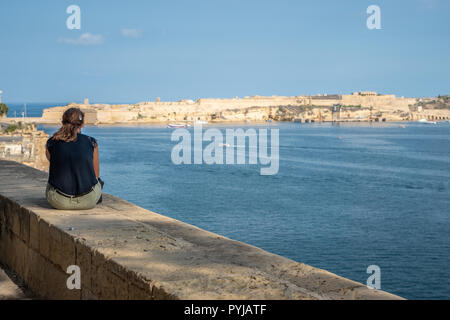 Wide angle view of a young lady sitting on the harbour wall looking looking at the view. Horizontal. Malta Grand hourbour - Stock Photo