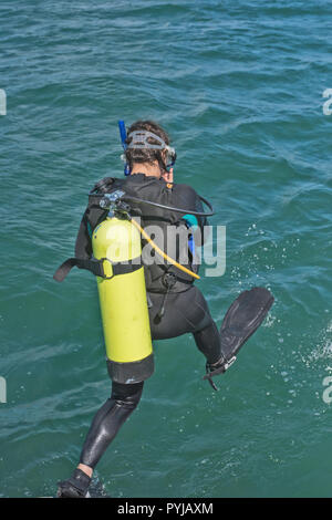 Scuba diver in wetsuit entering water from boat - Stock Photo