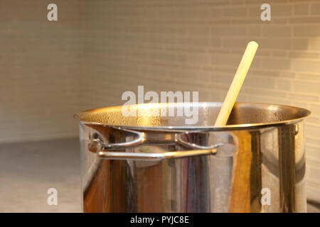 A large metal vat of soup or stew on the stove with a wooden handle in the kitchen - Stock Photo