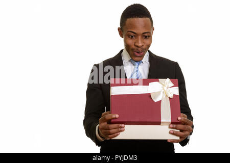 Young African businessman opening gift box and looking surprised - Stock Photo