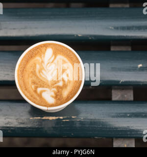 Paper cup of capupuccino coffee take-away, on wooden bench, with copy space for text, outdoor. - Stock Photo