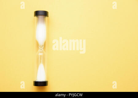 playing hourglass with white sand inside on yellow background - Stock Photo