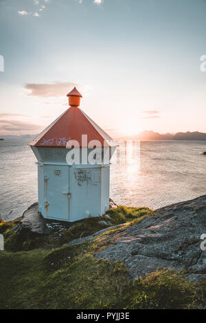 Sunrise and Sunset at Henningsvaer light house, fishing village located on several small islands in the Lofoten archipelago, Norway over a blue sky wi - Stock Photo