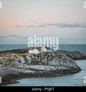 Sunrise and Sunset at Henningsvaer lighthouse with pink sky. The small fishing village located on several small islands in the Lofoten archipelago, No - Stock Photo