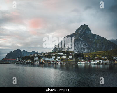 Norwegian fishing village Reine at the Lofoten Islands in Norway. Dramatic sunset clouds moving over steep mountain peaks in dusk. Reflection of stree