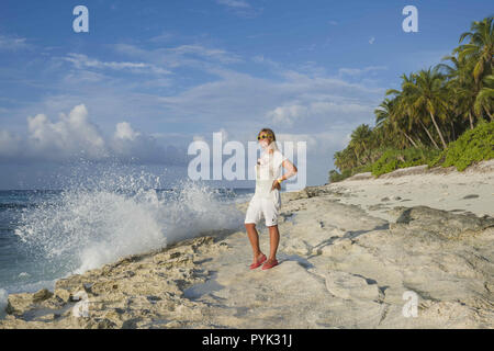 Fuvahmulah Island, Maldives, Asia. 16th Mar, 2018. Young woman in summer dress standing on a beach and looking to the horizon on an exotic tropical island Credit: Andrey Nekrasov/ZUMA Wire/Alamy Live News - Stock Photo