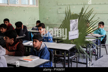 A picture of 14-year-old Khaled Abu Said, one of three Palestinian child killed the previous day in an Israeli air strike on the Gaza border, is seen on his seat in his classroom as other classmates attend a lesson in a school in Deir el-Balah in the central Gaza Strip. The three Palestinians who were killed on October 23, 2018 in an Israeli air strike according to the Palestinian health ministry, were buried today in Deir al-Balah. - Stock Photo