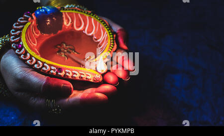 Diwali decorations with traditional Indian oil lamps with selective focus and yellow background. - Stock Photo