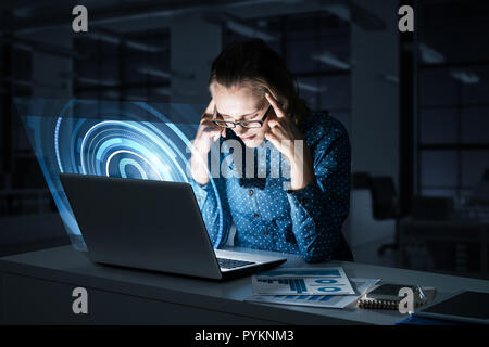 Beautiful blonde in dark office working on laptop and getting ne - Stock Photo