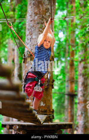 Brave young child in safety harness climb high on tree tops, pass hanging bridge obstacle in adventure rope park. Outdoor activity,  active lifestyle  - Stock Photo