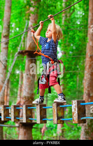 Brave young child in safety harness climb high on tree tops, pass hanging bridge obstacle in adventure rope park. Outdoor activity. - Stock Photo