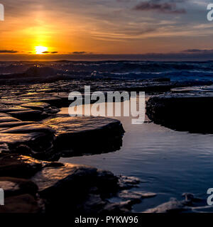 Waves crashing on rocks with pools water at sunset - Stock Photo