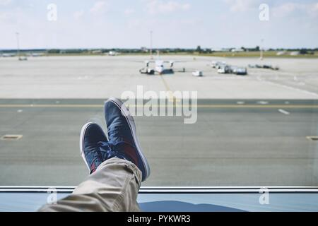 Man waiting at airport. Personal perspective of traveler from window to taxiways and runway. - Stock Photo
