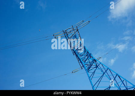 bottom view of the tower of power grids on blue sky background, High voltage, Electricity concept - Stock Photo