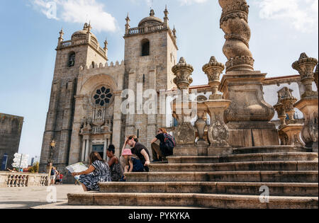 Porto, Portugal - 27 september, 2018: Group of tourists looks at map on stairs of Pillory of Porto against Se cathedral, Portugal - Stock Photo
