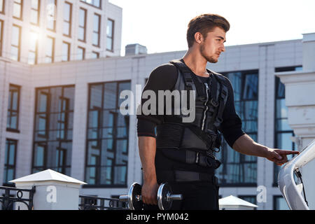 good looking fit man standing with dumbbell on the street - Stock Photo