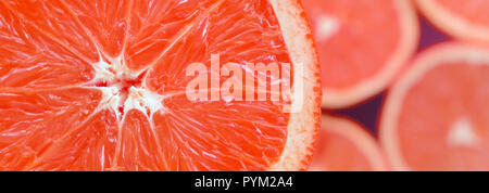 Top view of a fragment of the red grapefruit slice on the background of many blurred grapefruit slices. A saturated citrus texture image - Stock Photo