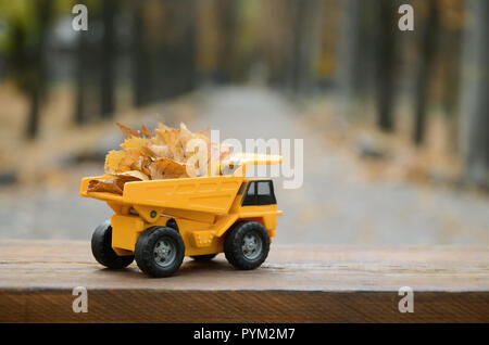 A small toy yellow truck is loaded with yellow fallen leaves. The car stands on a wooden surface against a background of a blurry autumn park. Cleanin - Stock Photo