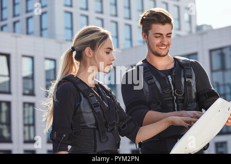 positive man and woman pushing on screen - Stock Photo