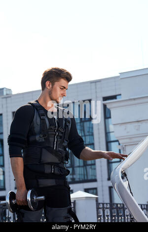 sporty strong guy is turning off the EMS device - Stock Photo