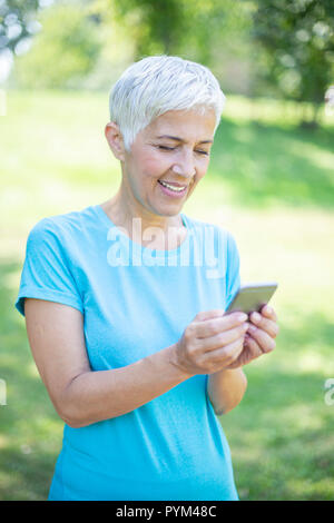 Portrait of senior woman in sports clothing  using smart phone outdoor - Stock Photo
