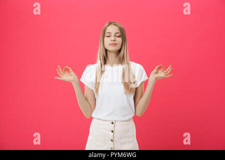Blonde beauiful young female makes mudra sign, relaxes after hard working day, keeps eyes shut, practises yoga against pink background. Young pretty woman meditates indoor. Relaxation concept. - Stock Photo