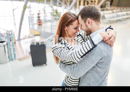 Loving couple embraces each other happily when they meet again at the airport terminal - Stock Photo