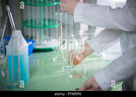 Chemical laboratory. Young woman holding a flask, pouring something using pipette - Stock Photo