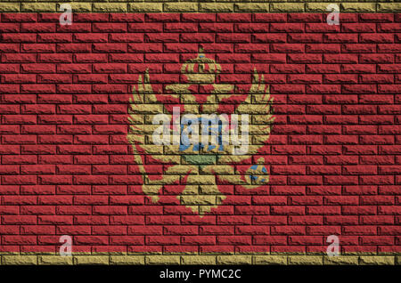 Montenegro flag is painted onto an old brick wall - Stock Photo