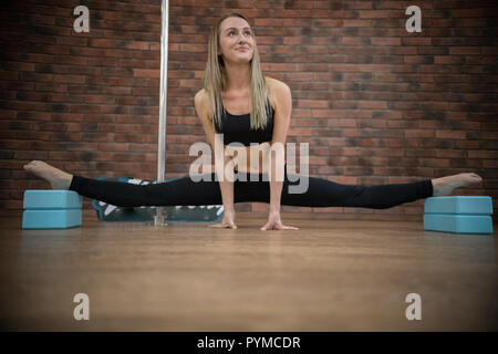 Young beatiful woman doing the splits in pole dance studio - Stock Photo