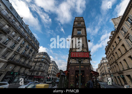 PARIS, 27 October 2018 - View of the typical stone apartment and houses at the Haussmann boulevard with an Metro station entrance and restaurant - Stock Photo