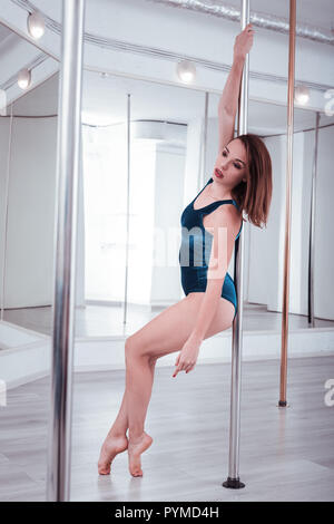 Red-haired pole dancer wearing nice bright unitard dancing near pole - Stock Photo