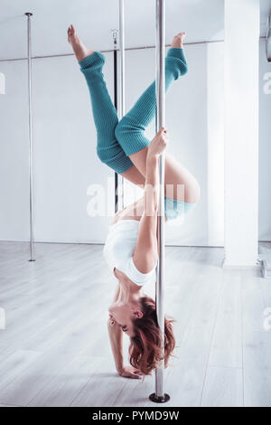Red-haired pole dancer wring short white top training all day long - Stock Photo