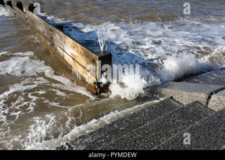 Waves breaking against timber groyne and concrete stepped revetment, Coastal sea defence scheme in Cleveleys on the Fylde coast in lancashire uk - Stock Photo