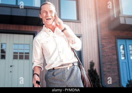 Stylish handsome man with tattoo on hand laughing while speaking by phone - Stock Photo