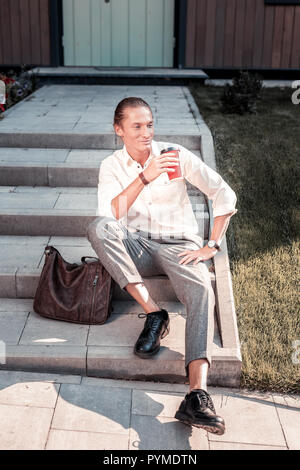Handsome stylish man sitting on the porch while waiting for his girlfriend - Stock Photo