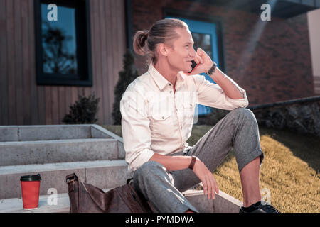 Man sitting on the stairs outside having coffee and speaking by phone - Stock Photo