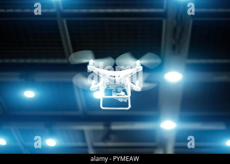 White drone in motion. Quadcopter flying inside a large warehouse - Stock Photo
