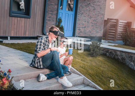 Modern father and daughter wearing virtual reality glasses and eating popcorn - Stock Photo