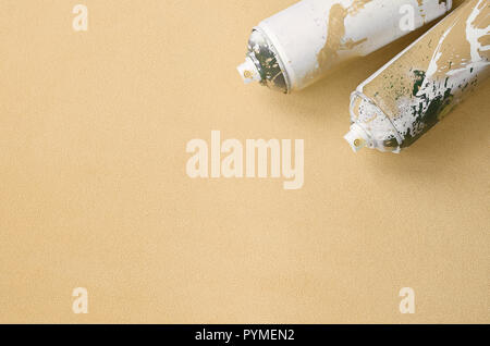 Some used blue aerosol spray cans with paint drips lies on a blanket of soft and furry light blue fleece fabric. Classic female design color. Graffiti - Stock Photo