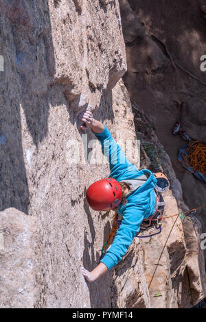 Aerial view of female climber with red helmet climbing a limestone route. Both hands grabbing rock. - Stock Photo